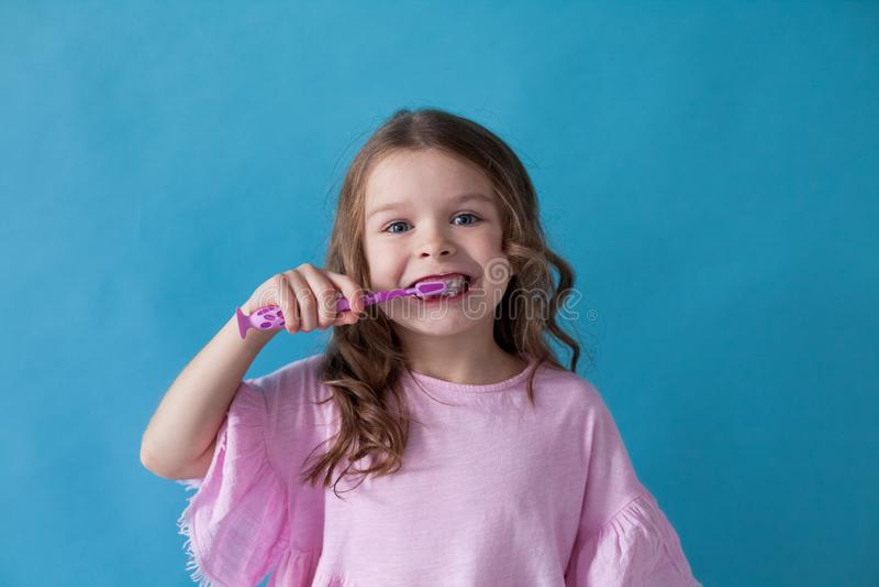 Μικρό κορίτσι που βουρτσίζει τα δόντια του με ένα ζούλιγμα οδοντοβουρτσών στοκ εικόνες