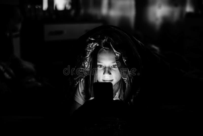 Μικρό κορίτσι που βρίσκεται στο κρεβάτι τη νύχτα και που εξετάζει την καμμένος οθόνη του smartphone στοκ φωτογραφία
