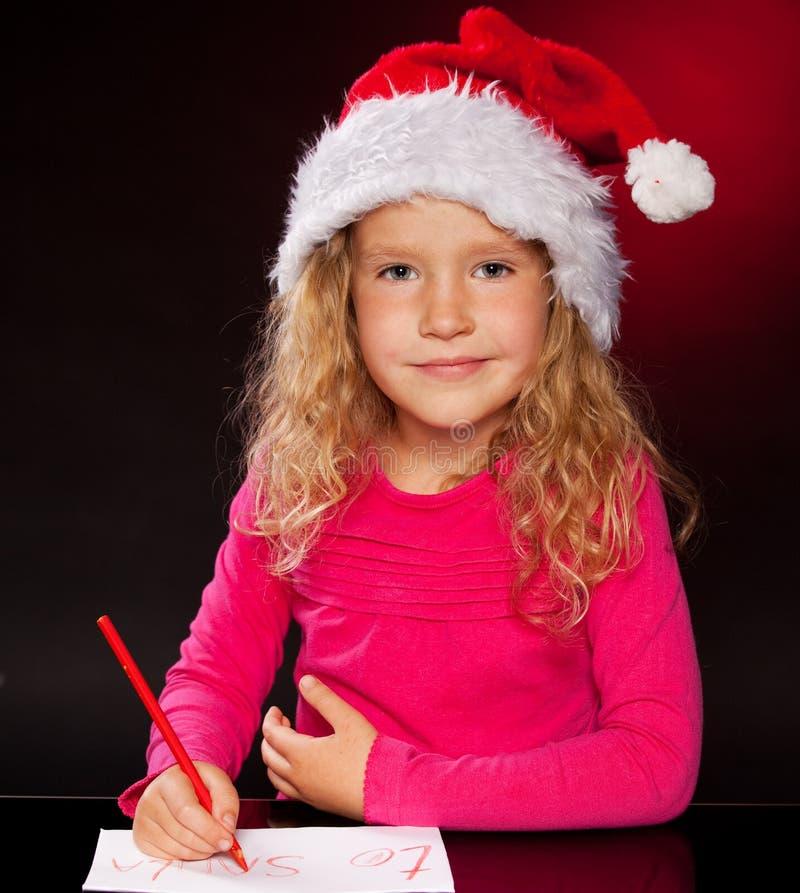 Μικρό κορίτσι που γράφει μια επιστολή σε Άγιο Βασίλη στοκ εικόνα με δικαίωμα ελεύθερης χρήσης
