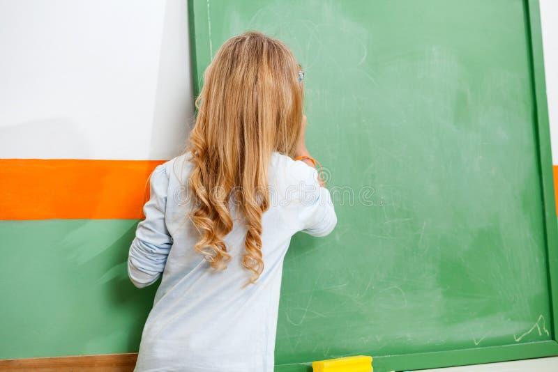 Μικρό κορίτσι που γράφει στον πίνακα κιμωλίας στην τάξη στοκ εικόνα