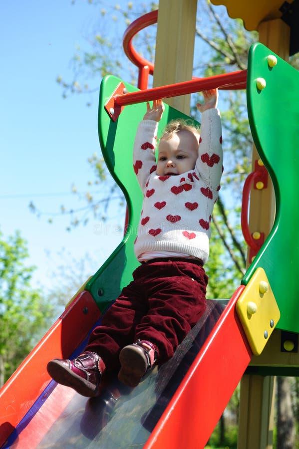 Μικρό κορίτσι που γλιστρά στην παιδική χαρά στοκ φωτογραφία