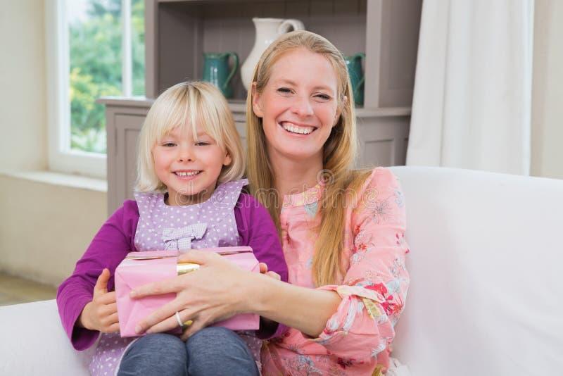 Μικρό κορίτσι που εκπλήσσει τη μητέρα της με το δώρο στοκ φωτογραφίες