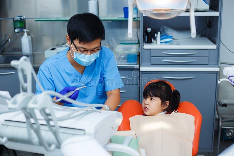 Μικρό κορίτσι που εξετάζει προσεκτικό το γιατρό οδοντιάτρων και το youn του στοκ εικόνες με δικαίωμα ελεύθερης χρήσης