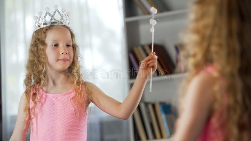 Μικρό κορίτσι που εξετάζει την αντανάκλαση καθρεφτών, που φορά το φανταχτερό φόρεμα πριγκηπισσών, μαγικό στοκ εικόνα