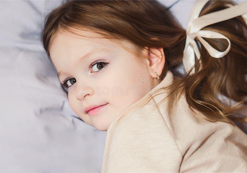 Μικρό κορίτσι που εξετάζει τη κάμερα στο κρεβάτι στοκ φωτογραφίες