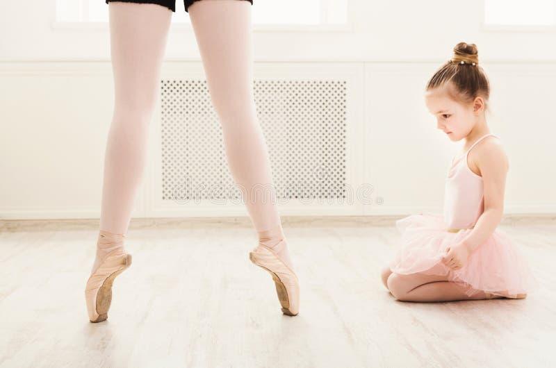 Μικρό κορίτσι που εξετάζει τον επαγγελματικό χορευτή μπαλέτου στοκ φωτογραφίες