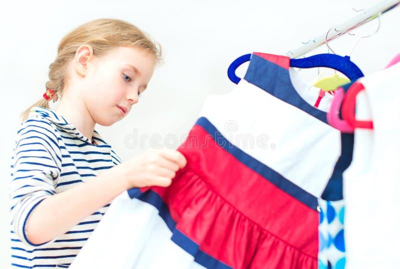 Μικρό κορίτσι που επιλέγει το φόρεμα στοκ εικόνες