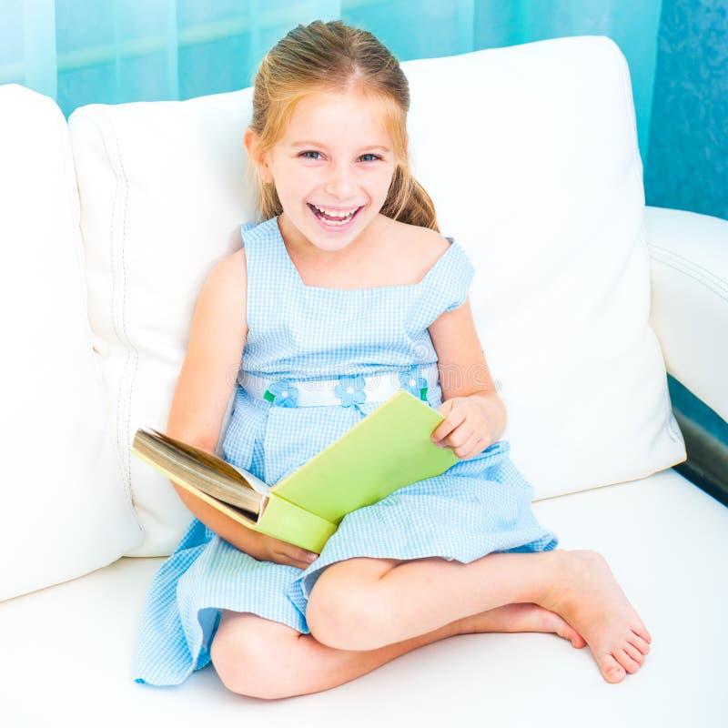 Μικρό κορίτσι που διαβάζει ένα βιβλίο στοκ εικόνα