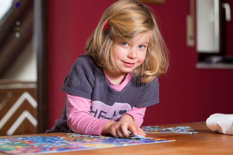 Μικρό κορίτσι που κάνει έναν γρίφο τορνευτικών πριονιών στοκ εικόνα