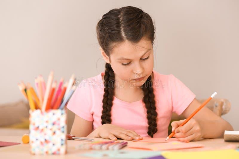 Μικρό κορίτσι που κάνει τη ευχετήρια κάρτα για τη μητέρα στο σπίτι στοκ εικόνες