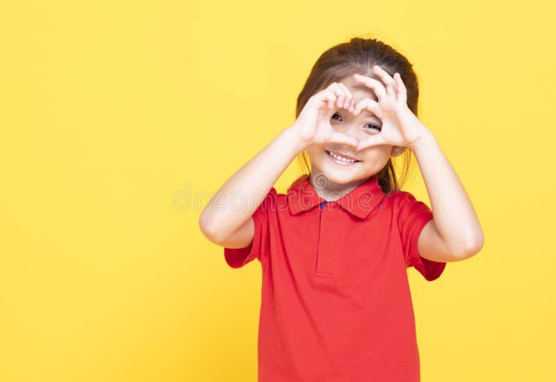 μικρό κορίτσι που κάνει τη μορφή καρδιών με το χέρι στοκ φωτογραφίες