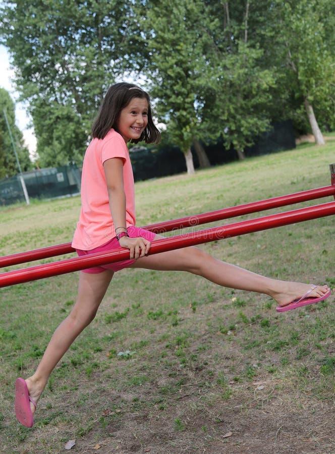 Μικρό κορίτσι που κάνει τις ασκήσεις γυμναστικής στους φραγμούς στοκ εικόνα