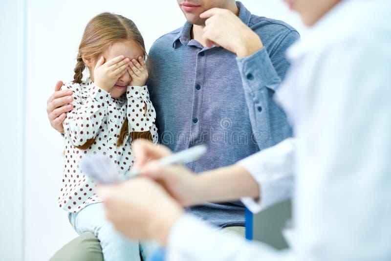 Μικρό κορίτσι που καλύπτει το πρόσωπο με το χέρι από το φόβο στοκ εικόνα