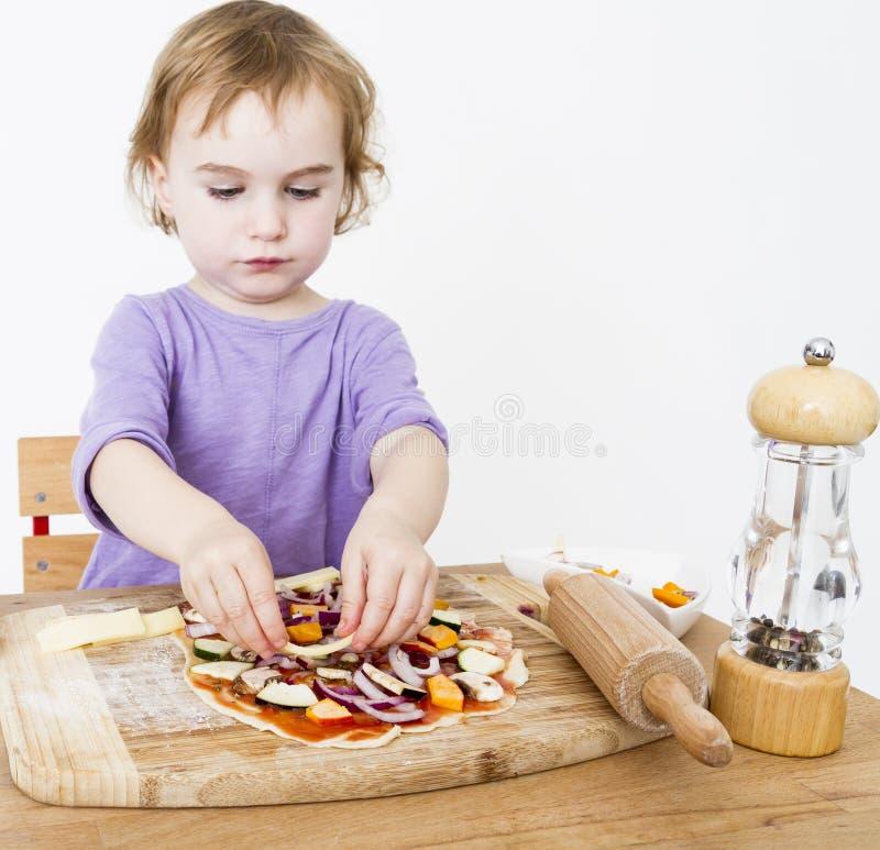 Μικρό κορίτσι που κατασκευάζει τη φρέσκια πίτσα στοκ φωτογραφίες με δικαίωμα ελεύθερης χρήσης
