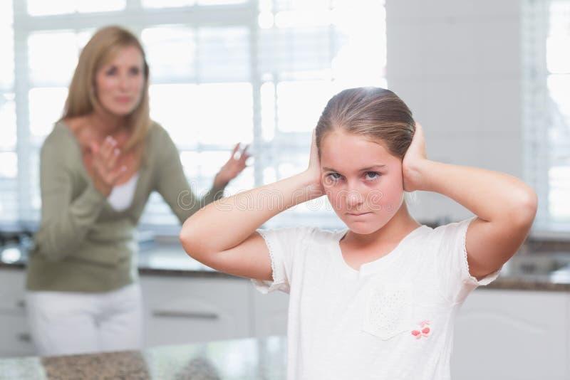 Μικρό κορίτσι που καλύπτει τα αυτιά της η κραυγή μητέρων της στοκ φωτογραφία