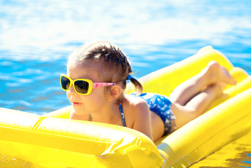 Μικρό κορίτσι που κολυμπά στο διογκώσιμο στρώμα παραλιών στοκ εικόνες