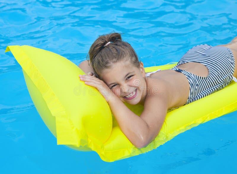Μικρό κορίτσι που κολυμπά στο διογκώσιμο στρώμα παραλιών στοκ εικόνες με δικαίωμα ελεύθερης χρήσης