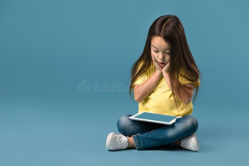 Μικρό κορίτσι που κρατά έναν κενό υπολογιστή ταμπλετών στοκ φωτογραφία με δικαίωμα ελεύθερης χρήσης