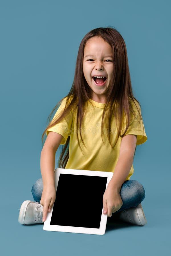 Μικρό κορίτσι που κρατά έναν κενό υπολογιστή ταμπλετών στοκ φωτογραφία