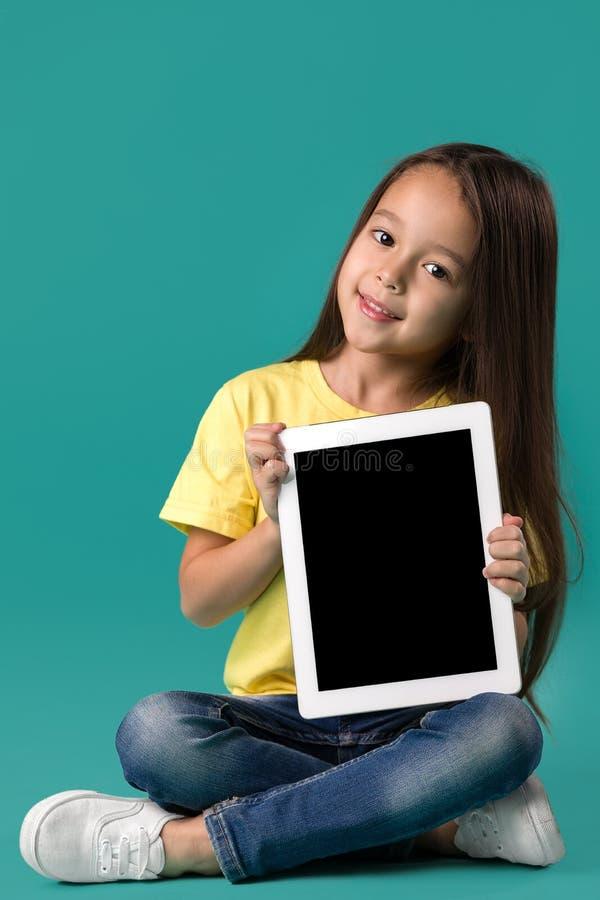 Μικρό κορίτσι που κρατά έναν κενό υπολογιστή ταμπλετών στοκ εικόνα με δικαίωμα ελεύθερης χρήσης