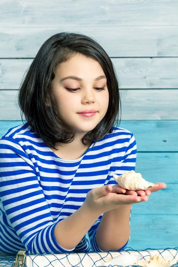 Μικρό κορίτσι που κρατά ένα κοχύλι στοκ εικόνες
