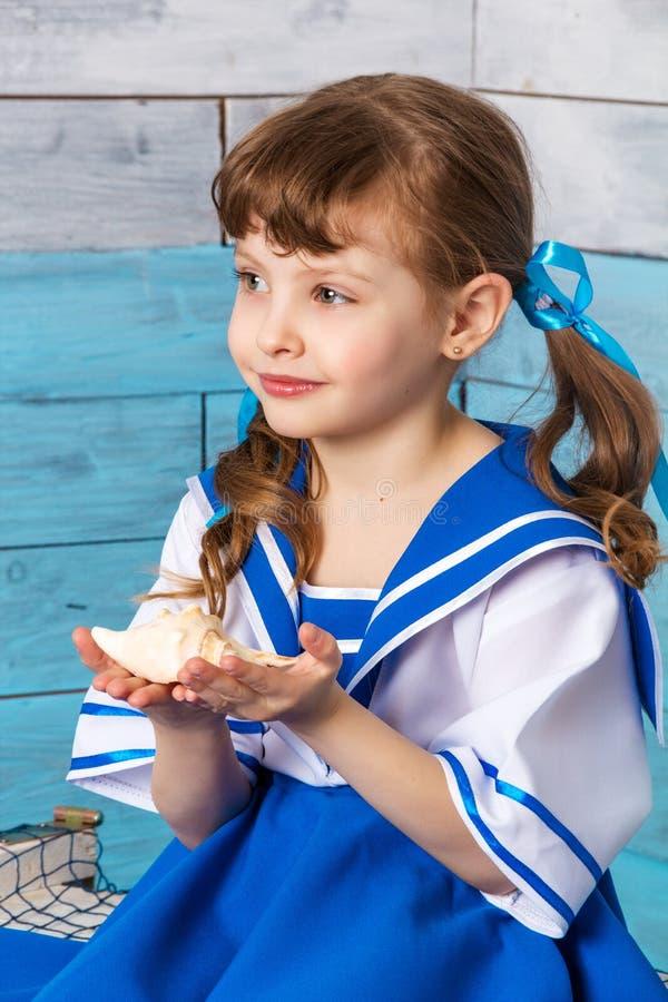 Μικρό κορίτσι που κρατά ένα κοχύλι στοκ φωτογραφίες
