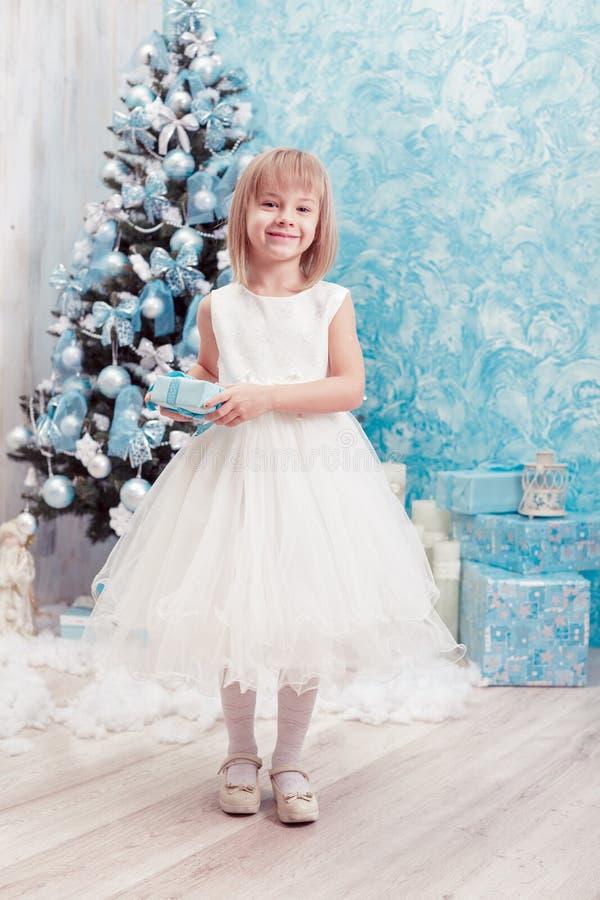 Μικρό κορίτσι που κρατά ένα μαγικό κιβώτιο δώρων Χριστουγέννων στοκ φωτογραφία