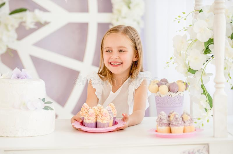 Μικρό κορίτσι που κρατά ένα ρόδινο πιάτο με τα γλυκά κέικ στο φραγμό καραμελών στοκ φωτογραφία