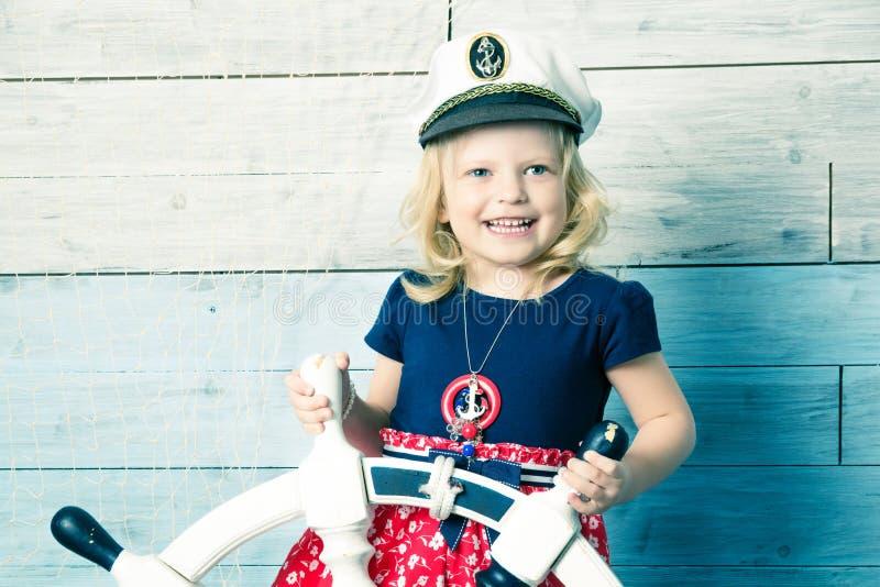 Μικρό κορίτσι που κρατά ένα τιμόνι στοκ φωτογραφίες