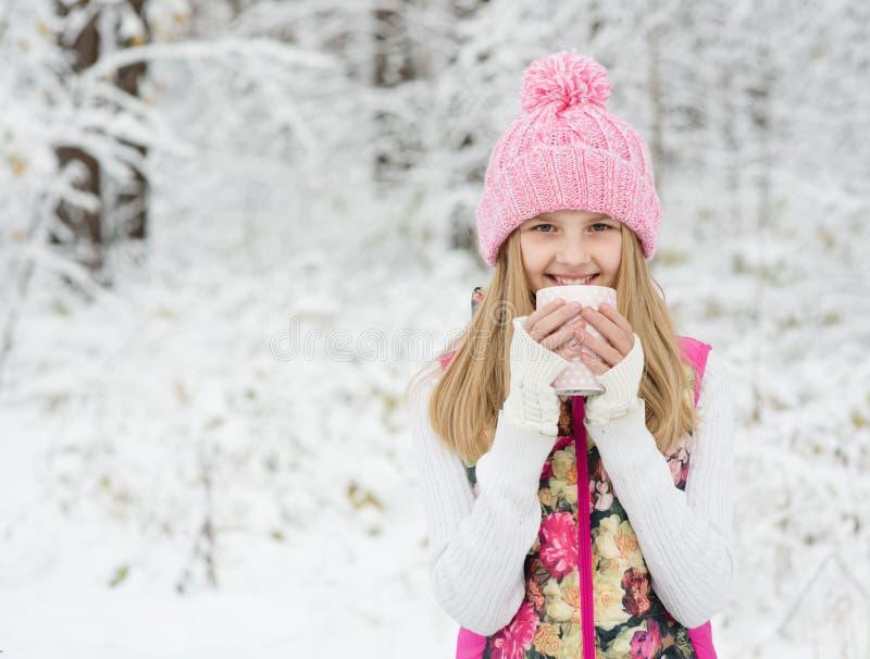 Μικρό κορίτσι που κρατά ένα φλυτζάνι του ζεστού ποτού και του χαμόγελου στοκ φωτογραφίες με δικαίωμα ελεύθερης χρήσης