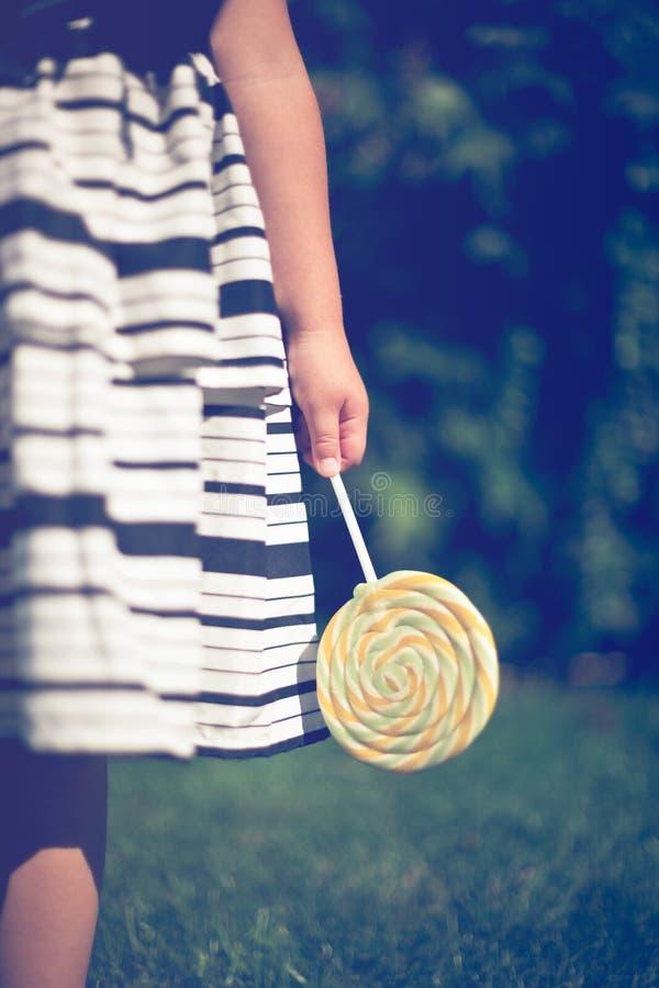 Μικρό κορίτσι που κρατά ένα lollipop στο χέρι της στοκ εικόνα με δικαίωμα ελεύθερης χρήσης