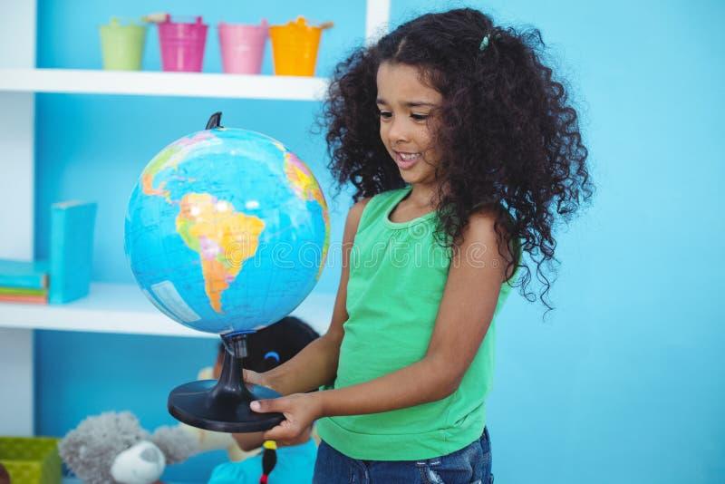 Μικρό κορίτσι που κρατά μια σφαίρα του κόσμου στοκ φωτογραφία με δικαίωμα ελεύθερης χρήσης