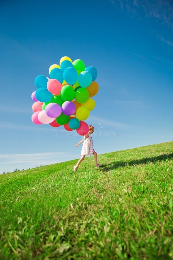 Μικρό κορίτσι που κρατά τα ζωηρόχρωμα μπαλόνια. Παιχνίδι παιδιών σε ένα πράσινο στοκ φωτογραφίες