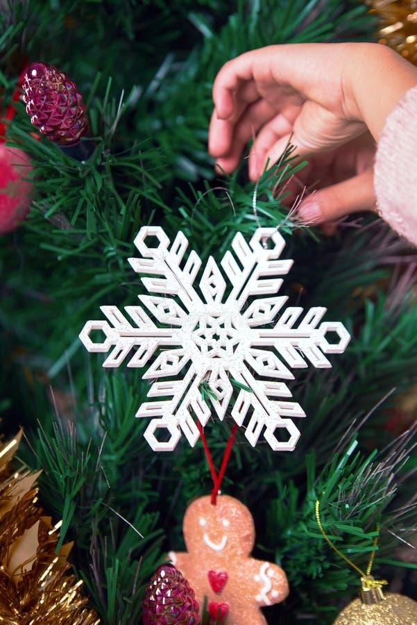 Μικρό κορίτσι που κρεμά διακοσμητικό snowflake στο χριστουγεννιάτικο δέντρο στοκ εικόνα