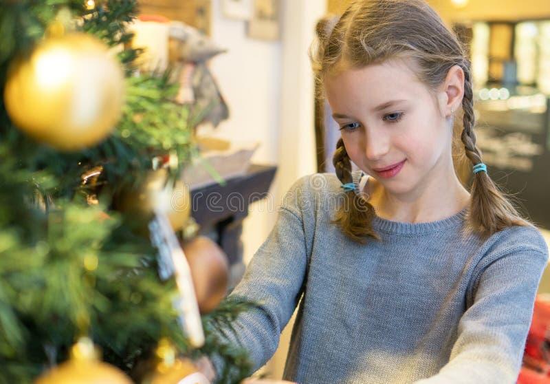 Μικρό κορίτσι που κρεμά τη διακοσμητική σφαίρα στοκ εικόνες
