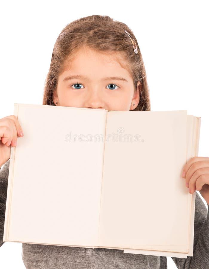 Μικρό κορίτσι που κρυφοκοιτάζει από πίσω από ένα ανοικτό βιβλίο στοκ φωτογραφίες με δικαίωμα ελεύθερης χρήσης
