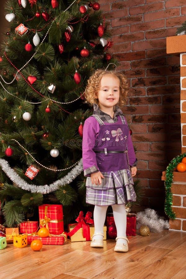 Μικρό κορίτσι που μένει κοντά στο χριστουγεννιάτικο δέντρο στοκ φωτογραφία με δικαίωμα ελεύθερης χρήσης