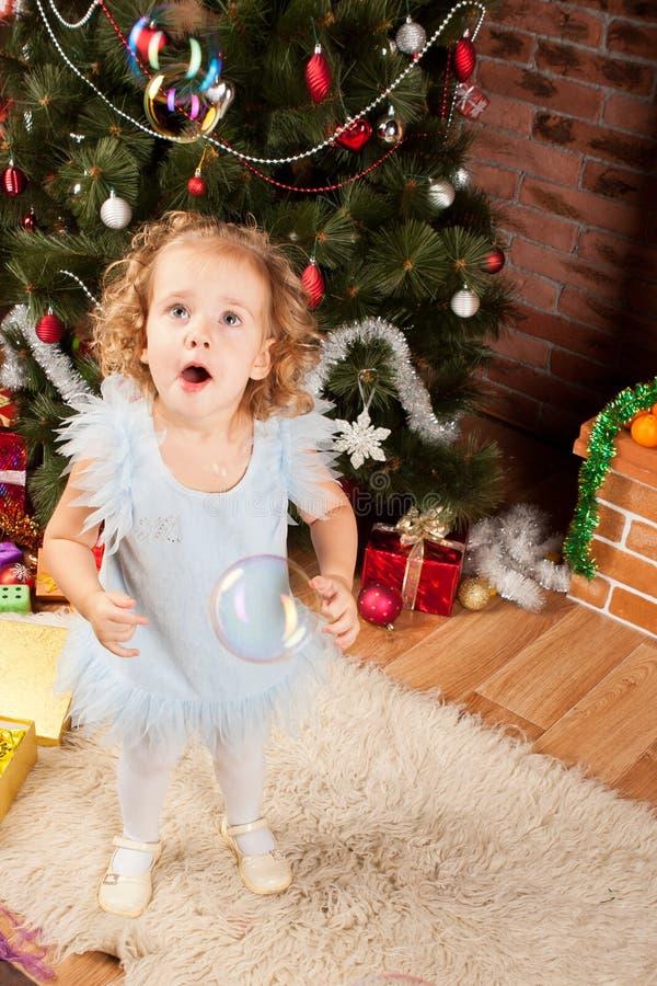Μικρό κορίτσι που μένει κοντά στο χριστουγεννιάτικο δέντρο στοκ φωτογραφίες