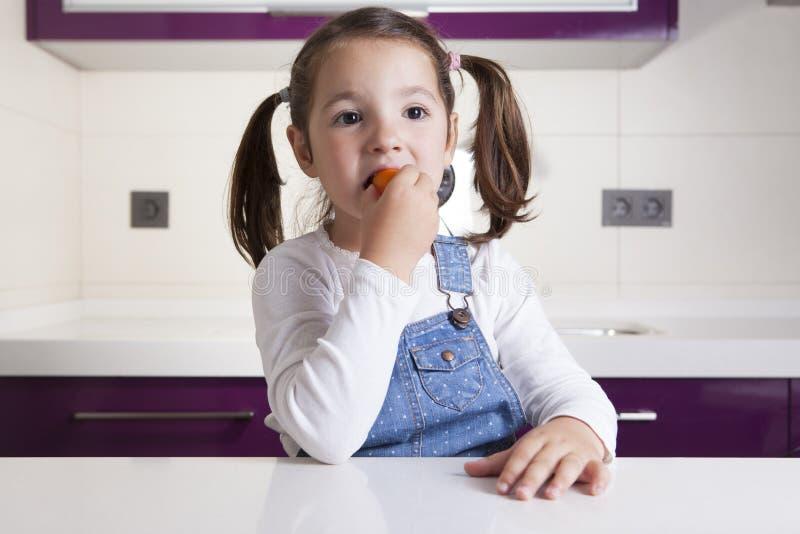 Μικρό κορίτσι που δοκιμάζει μια ακατέργαστη ζωηρόχρωμη ντομάτα κερασιών στοκ εικόνες