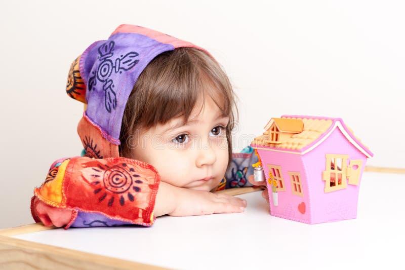Μικρό κορίτσι που ονειρεύεται για το σπίτι και την οικογένεια στοκ φωτογραφίες