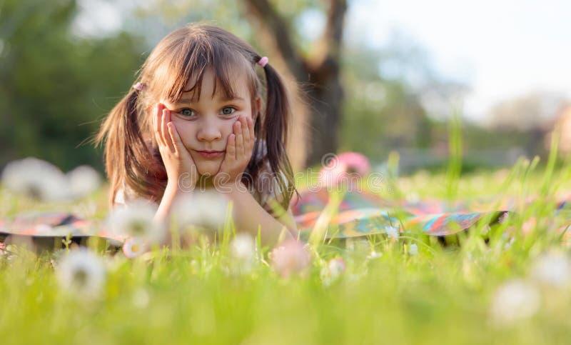 Μικρό κορίτσι που ονειρεύεται στον κήπο στοκ εικόνες με δικαίωμα ελεύθερης χρήσης