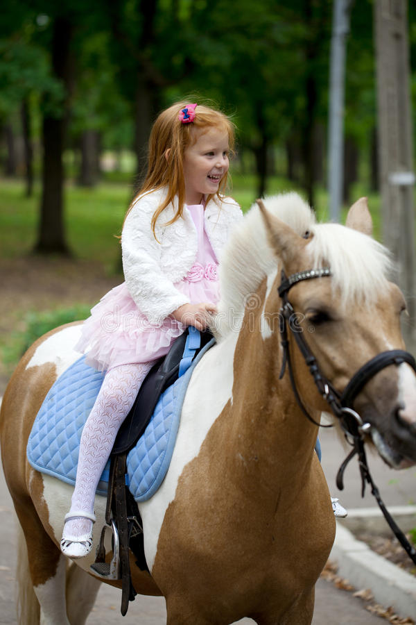 Μικρό κορίτσι που οδηγά σε ένα πόνι σε ένα πάρκο πόλεων στοκ εικόνες