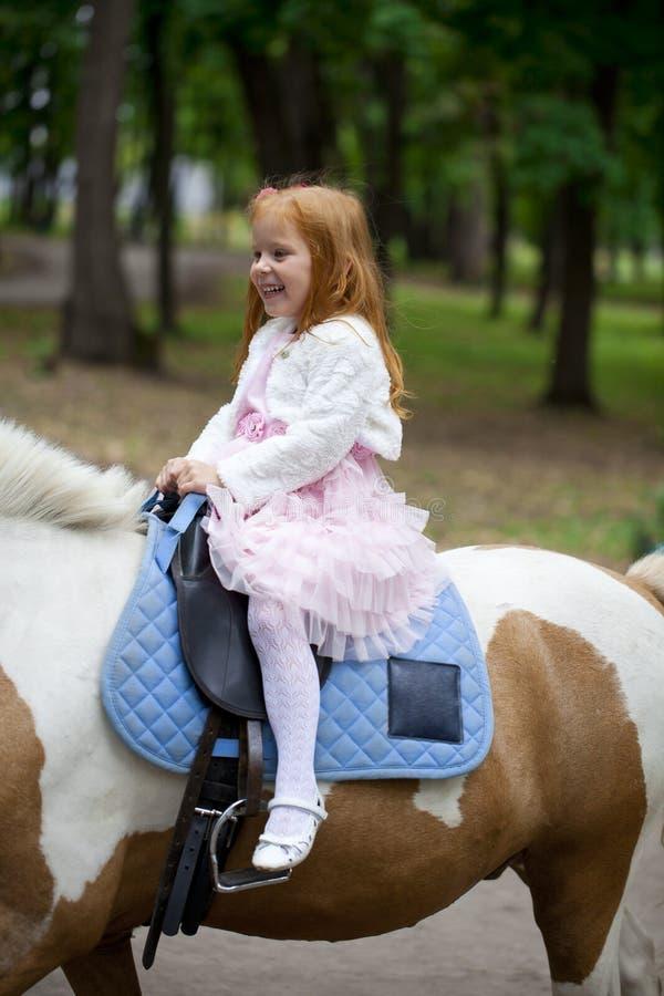 Μικρό κορίτσι που οδηγά σε ένα πόνι σε ένα πάρκο πόλεων στοκ εικόνες με δικαίωμα ελεύθερης χρήσης
