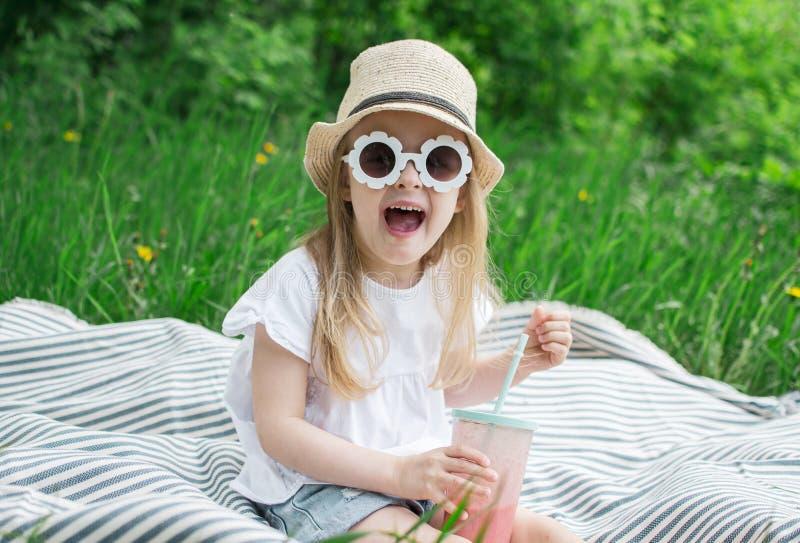 Μικρό κορίτσι που πίνει τον εύγευστο καταφερτζή φραουλών με το γάλα και το παγωτό στοκ εικόνες με δικαίωμα ελεύθερης χρήσης
