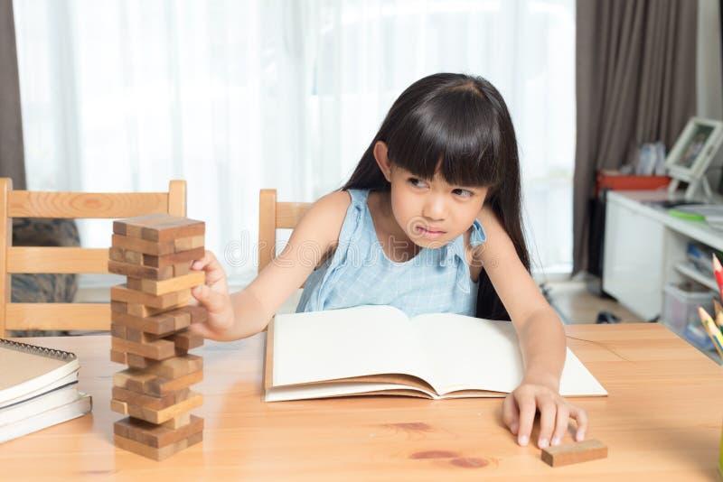 Μικρό κορίτσι που παίζει το ξύλινο παιχνίδι σωρών φραγμών στοκ φωτογραφία