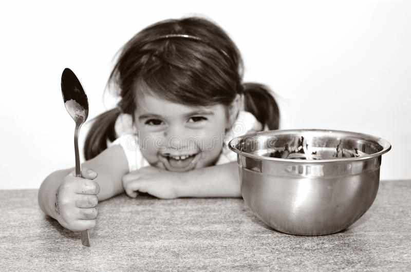 Μικρό κορίτσι που παίρνει πιασμένο τελειώνοντας όλη την κρέμα σοκολάτας στοκ φωτογραφία