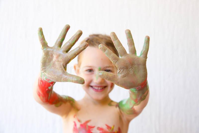 Μικρό κορίτσι που παρουσιάζει χέρια της, που καλύπτονται στο χρώμα δάχτυλων στοκ εικόνες