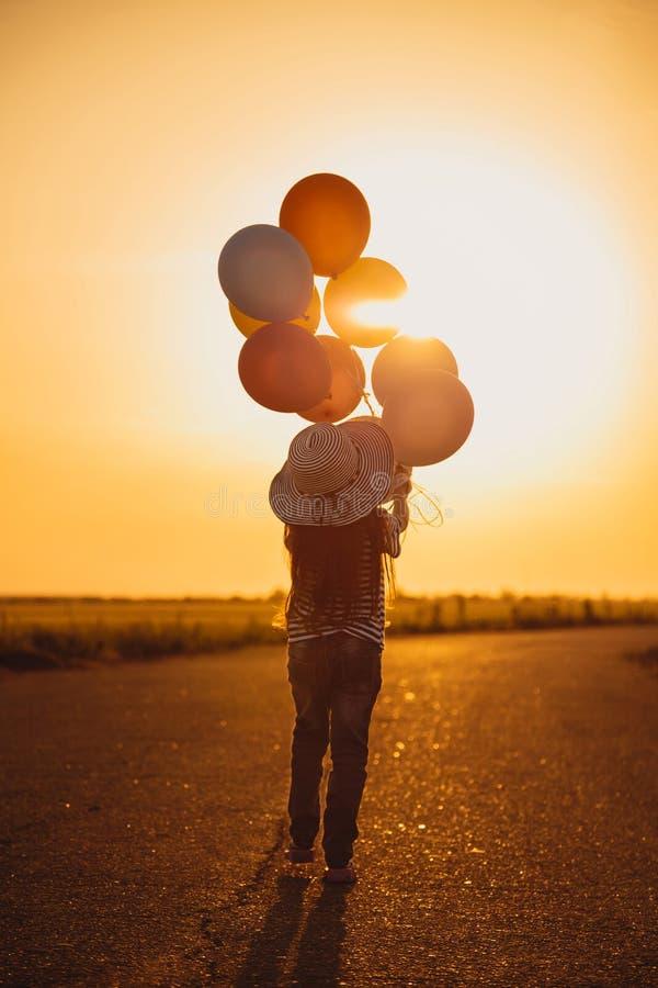 Μικρό κορίτσι που περπατά με τα ζωηρόχρωμα μπαλόνια στο δρόμο στον τομέα στο ηλιοβασίλεμα Θερινά ελευθερία και ταξίδι Έννοια ελπί στοκ εικόνα