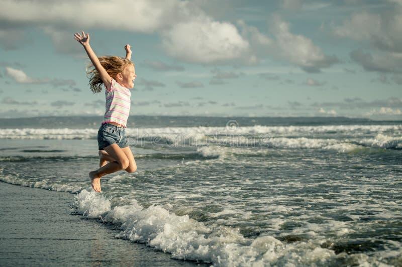 Μικρό κορίτσι που πηδά στην παραλία στην μπλε ακροθαλασσιά στοκ φωτογραφία