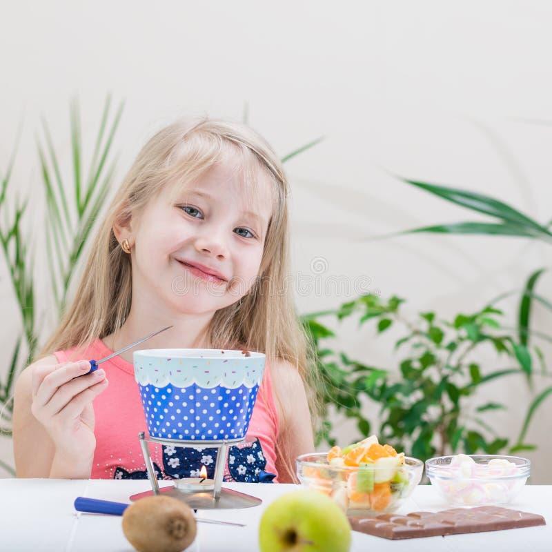 Μικρό κορίτσι που προετοιμάζει και που τρώει fondue σοκολάτας στοκ εικόνες